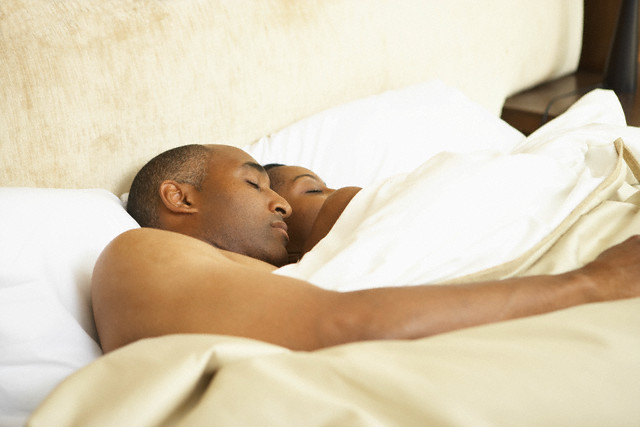 African American couple sleeping in bed --- Image by © RK Studio/Blend Images/Corbis