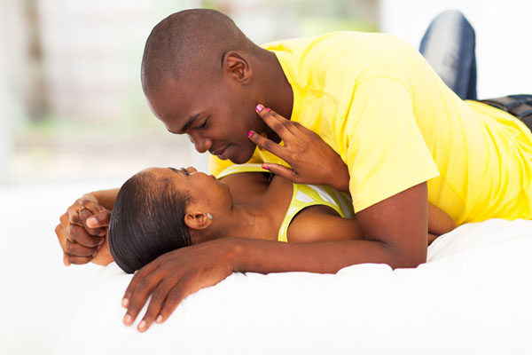 intimate young african couple in bed