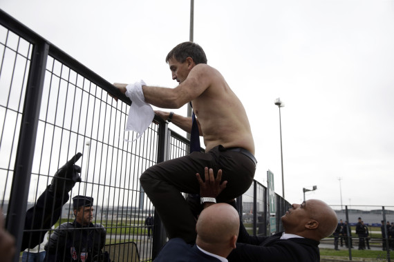 Human Resources Director of Air France Xavier Broseta, shirtless, tries to cross a fence, helped by security and police officers, after several hundred of employees invaded the offices of Air France, interrupting the meeting of the Central Committee (CCE) in Roissy-en-France, on October 5, 2015. Air France-KLM unveiled a revamped restructuring plan on October 5 that could lead to 2,900 job losses after pilots for the struggling airline refused to accept a proposal to work longer hours. AFP PHOTO / KENZO TRIBOUILLARD